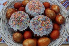 Cakes en geschilderde eieren in een witte mand stock afbeelding