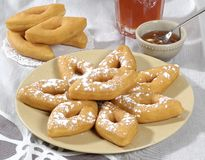 Cakes and Honey. Diamond shaped puffed pastries garnished with sugar. A small bowl of honey sits in the background Stock Photography