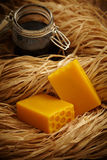 Cakes of honey soap. Cakes of honeycombed honey soap with jar of honey in hay or straw Royalty Free Stock Photos