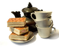 Cakes, kettle and three cups Stock Images