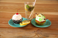 Cakes and lemonade in a glass worth on  wooden table Stock Photo