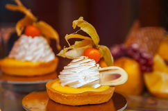 Cakes with meringue and berries of cape gooseberry Royalty Free Stock Photos