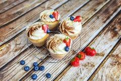 Cakes met room en bestrooid met cacao, en aardbeien en bosbessen Stock Foto