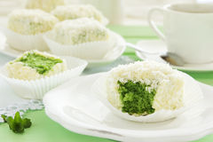 Cakes petit fours with tea. And coconut match Royalty Free Stock Photography