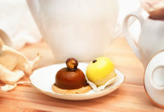 Cakes. Two cakes on a saucer on a light background with white ware Royalty Free Stock Photography