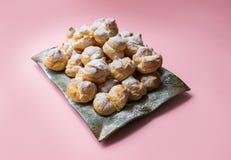 Cakes profiteroles met gepoederde suiker op een roze achtergrond worden bestrooid die Eigengemaakte eclairs royalty-vrije stock afbeeldingen