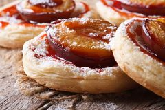 Cakes of puff pastry with plums macro horizontal Stock Photos