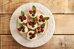 Cakes with raspberries and blueberries on a plate. On wooden background - top view Stock Image