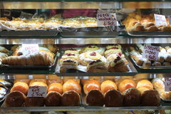 Cakes in showcase. Italian pastry shop with different baba, donuts, jelly, cakes with fruits and berries. Stock Photo