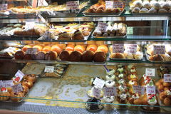 Cakes in showcase. Italian pastry shop with different baba, donuts, jelly, ice cream, cakes with fruits. Stock Photos