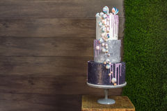 Cakes to order. Beautiful tiered birthday cake on a dark wooden background Royalty Free Stock Photography