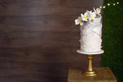 Cakes to order. Beautiful tiered birthday cake on a dark wooden background Stock Image