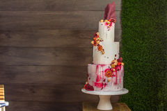 Cakes to order. Beautiful tiered birthday cake on a dark wooden background Royalty Free Stock Photo