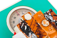 Cakes on weight scale Royalty Free Stock Photos
