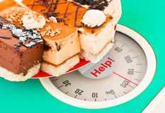 Cakes on weight scale and word Help Stock Image