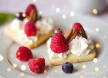 Cakes with whipped cream and berries. Holiday lights. stock photos