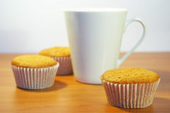 Cakes and white cup of tea Stock Photos