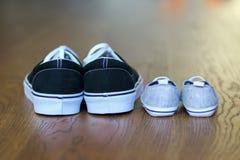 Calçados casuais do pai e do filho que ficam em seguida no assoalho de madeira imagens de stock