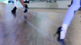 Calçados pretos à moda em mulheres dos pés, close-up das sapatas que vão ao longo da passarela, sapatas das coleções na semana de filme