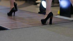 Calçados pretos em mulheres dos pés, close-up das sapatas que vão ao longo da passarela, coleções footgear na semana de moda video estoque