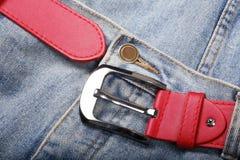 Calças de brim com correia vermelha Fotografia de Stock Royalty Free