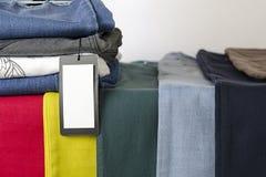calças de brim 9 cores diferentes, fundo das calças de brim, o fundo da roupa, etiqueta vazia foto de stock