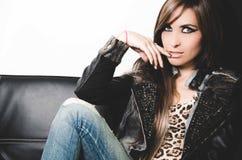 Calças de brim da sarja de Nimes, parte superior 'sexy' do leopardo e casaco de cabedal vestindo morenos, sentando-se no sofá que Fotografia de Stock