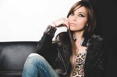 Calças de brim da sarja de Nimes, parte superior 'sexy' do leopardo e casaco de cabedal vestindo morenos, sentando-se no sofá que Imagens de Stock