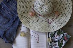 Calças de brim do estilo de vida do conceito do curso da vista superior, chapéu no fundo de madeira imagem de stock