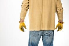 Calças de brim do homem e luvas vestindo do trabalho Imagens de Stock Royalty Free