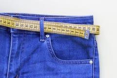 Calças de brim e assunto de medição para a perda de peso no fundo amarelo imagem de stock royalty free