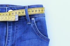 Calças de brim e assunto de medição para a perda de peso no fundo azul fotos de stock