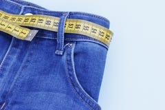 Calças de brim e close-up de medição da fita, conceito do estilo de vida saudável e peso de perda, espaço da cópia fotografia de stock