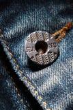 Calças de brim e o botão imagens de stock
