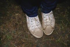 Calças de brim e sapatilhas vestindo da pessoa Fotos de Stock