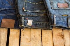 Calças de brim no espaço de madeira do fundo Imagem de Stock