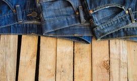 Calças de brim no espaço de madeira do fundo Imagens de Stock