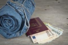 Calças de brim, passaporte e muito dinheiro imagem de stock royalty free