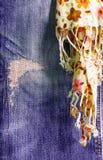 Calças de brim rasgadas com lenço Imagem de Stock Royalty Free