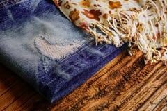 Calças de brim rasgadas com lenço Foto de Stock Royalty Free