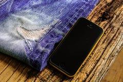 Calças de brim rasgadas com móbil Fotos de Stock Royalty Free