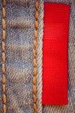 Calças de ganga com o close-up vermelho da etiqueta Foto de Stock Royalty Free
