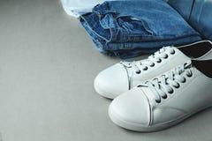 Calças de ganga e sapatilhas brancas no fundo cinzento foto de stock