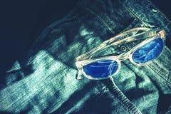 Calças de ganga e vidros de sol Fotos de Stock