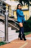 Calças de ganga vestindo da jovem mulher bonita elegante, e peúgas listradas longas do joelho Fotografia de Stock Royalty Free