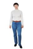 Calças de ganga vestindo da mulher escultural e Turtleneck branco foto de stock