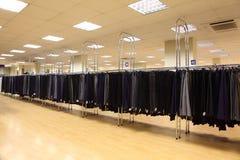 Calças dos homens da fileira em ganchos na loja Imagem de Stock