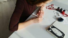 Calígrafo que trabalha na oficina, criando a inscrição nova para o cartão video estoque
