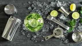 Cal de cristal del cóctel, menta, hielo La bebida que hace la barra equipa la coctelera Foto de archivo