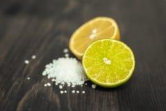 Cal, limão e sal cortados frescos na tabela de madeira Fotografia de Stock